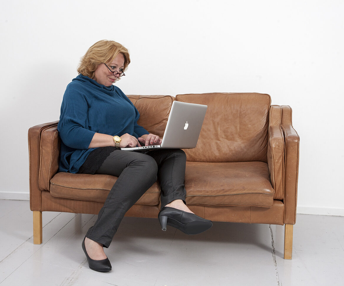 Karen-Marie sidder på en sofa med sin mac og skriver løs