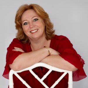 Karen-Marie på hvid stol smiler til pressen